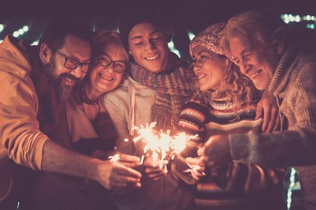 Grupo de pessoas da família comemorando o ano novo com estrelinhas de iluminação ao ar livre