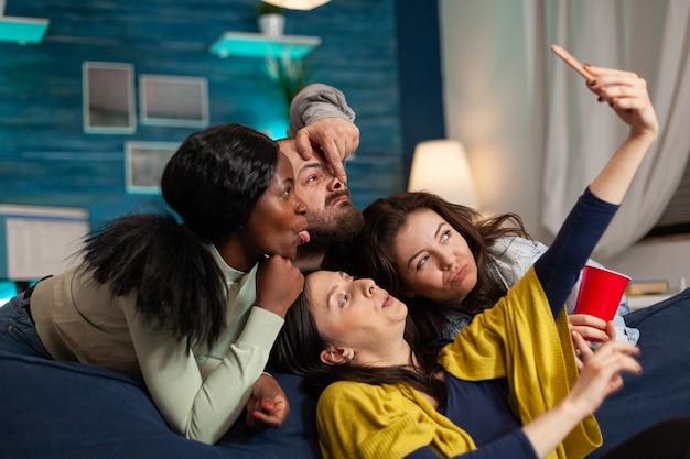 Grupo de pessoas da raça mista tirando fotos com o telefone enquanto está sentado no sofá na sala de estar, passando um tempo juntos. amigos multirraciais postando selfie na internet compartilhando com outra pessoa.