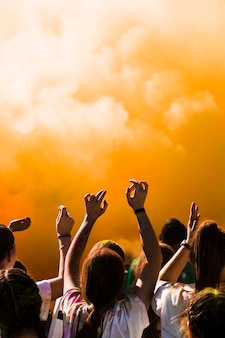 Grupo de pessoas dançando na frente de explosão de pó de holi