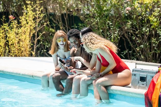 Grupo de pessoas de diferentes etnias, em trajes de banho, olhando para o celular na beira de uma piscina