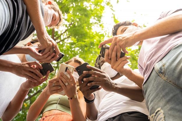 Grupo de pessoas de diferentes etnias, usando telefones celulares e usando máscaras de proteção