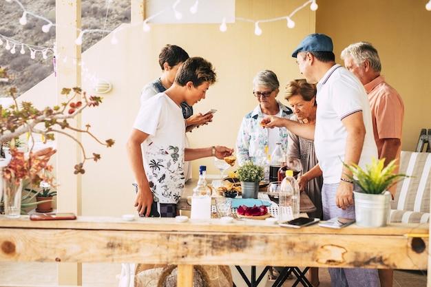 Grupo de pessoas de diferentes idades, de adolescente a adulto, se divertindo juntos, comendo comida e bebendo em amizade em casa ao ar livre no terraço