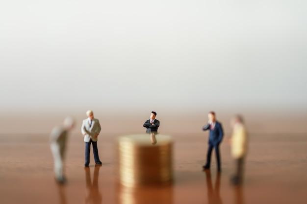 Grupo de pessoas de figura em miniatura do empresário em pé ao redor da pilha de moedas na mesa de madeira.