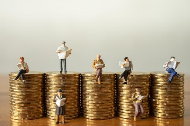 Grupo de pessoas de figura em miniatura do empresário figura lendo livro e jornal na pilha de moedas.