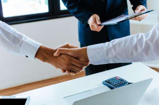 Grupo de pessoas de negócios aperto de mão depois de terminar reunião de negócios na sala de reuniões no escritório
