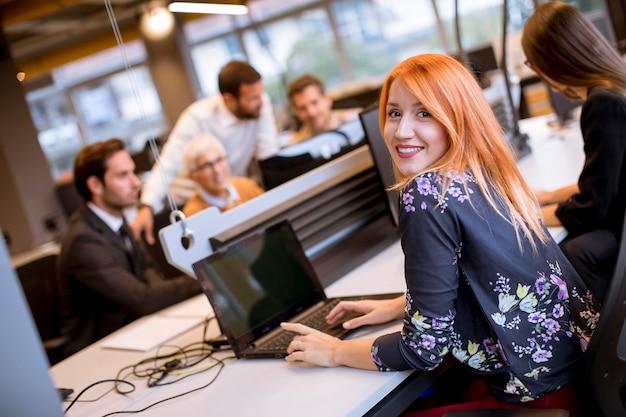 Grupo de pessoas de negócios com adultos jovens e colega de mulher sênior na reunião no interior do escritório moderno brilhante