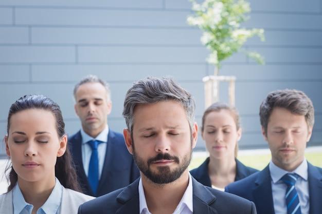 Grupo de pessoas de negócios com os olhos fechados