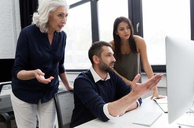 Grupo de pessoas de negócios, discutindo o plano financeiro à mesa em um escritório