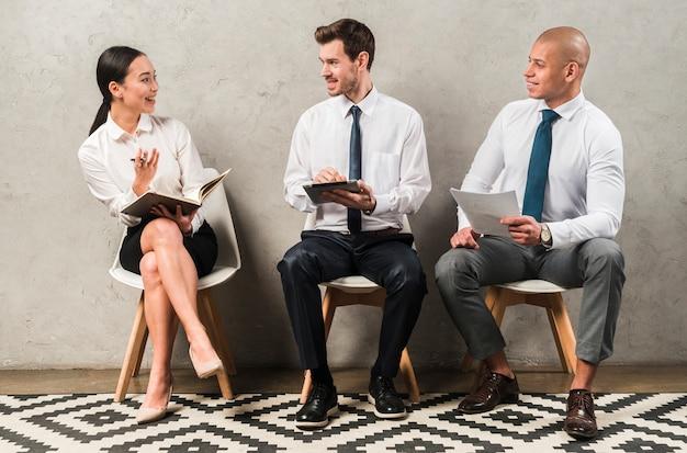Grupo de pessoas de negócios, sentado na cadeira, comunicando-se uns com os outros