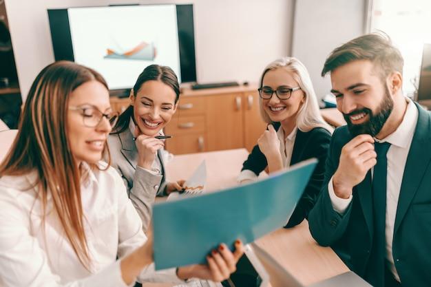 Grupo de pessoas de negócios, sentado na sala de reuniões e olhando para o gráfico.