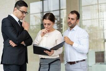 Grupo de pessoas de negócios sério, lendo o documento
