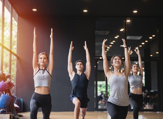 Grupo de pessoas de raça mista praticando ioga meditando juntos para estilo de vida saudável no clube de fitness
