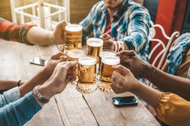 Grupo de pessoas desfrutando e brindando uma cerveja no pub da cervejaria - conceito de amizade com os jovens se divertindo juntos