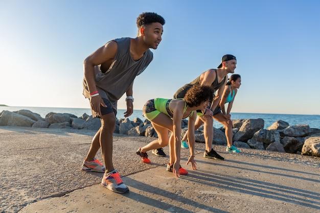 Grupo de pessoas desportivas se preparando para correr uma maratona