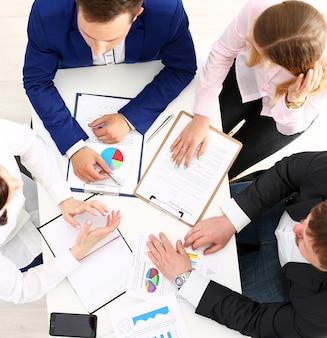 Grupo de pessoas discutir plano no local de trabalho closeup