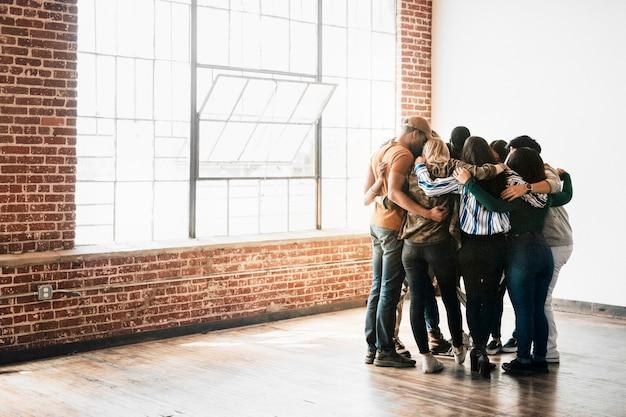 Grupo de pessoas diversas mantendo as mãos umas nas outras