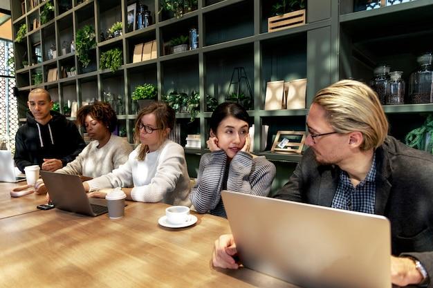 Grupo de pessoas diversas, tendo uma reunião de negócios