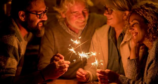 Grupo de pessoas e família comemorando alguma festa ou ano novo juntos no terraço da casa - quatro estrelinhas no meio juntos