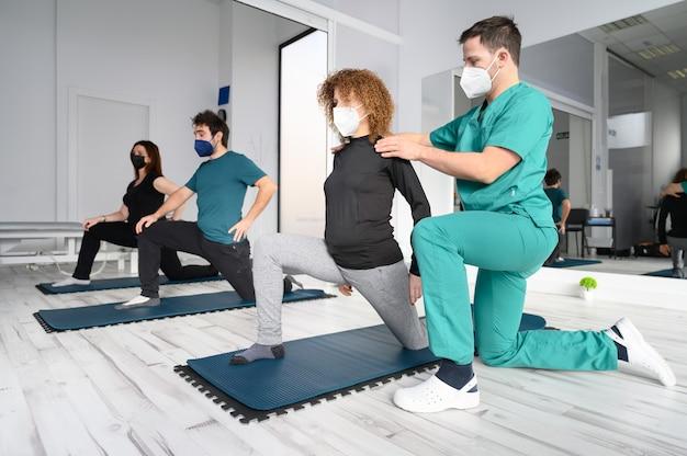 Grupo de pessoas em colchonetes de ioga assistidas por fisioterapeuta na clínica de reabilitação.