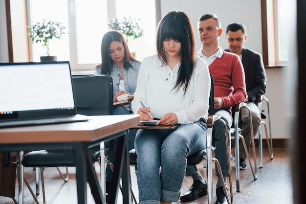 Grupo de pessoas em conferência de negócios em sala de aula moderna durante o dia