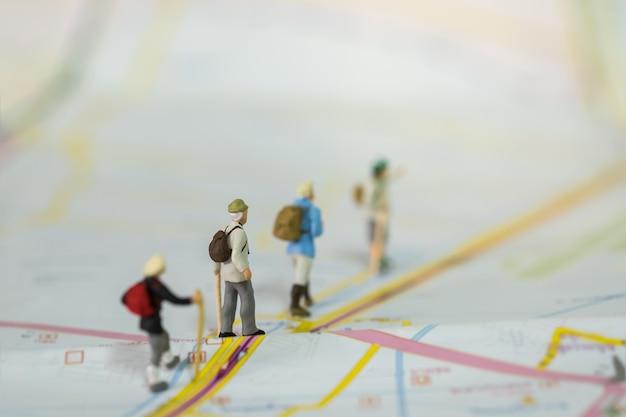 Grupo de pessoas em miniatura de viajantes com mochila caminhando no mapa
