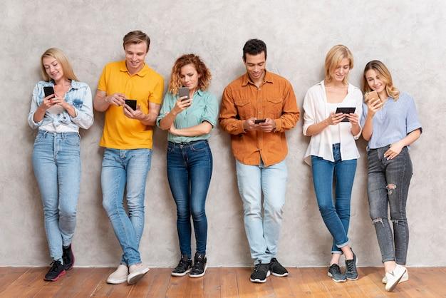 Grupo de pessoas em pé e verificando dispositivos