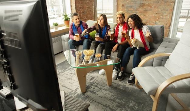 Grupo de pessoas empolgadas assistindo a um campeonato de jogos esportivos em casa