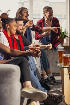Grupo de pessoas empolgadas assistindo futebol, jogo de esporte em casa