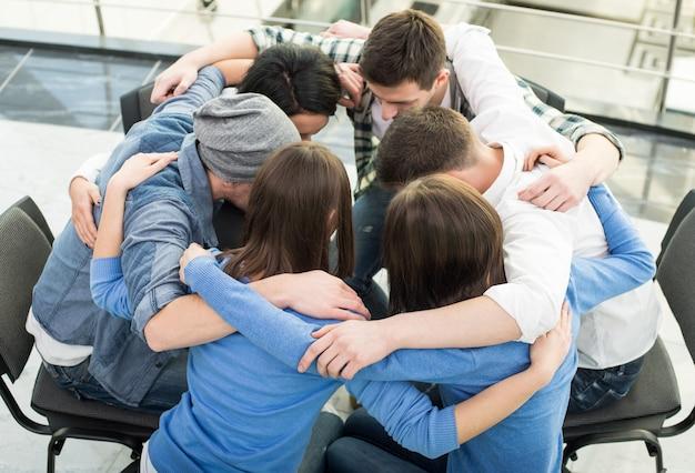 Grupo de pessoas estão sentados abraçando em círculo.
