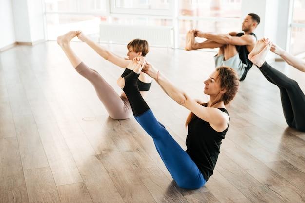 Grupo de pessoas esticando as pernas e praticando ioga no estúdio