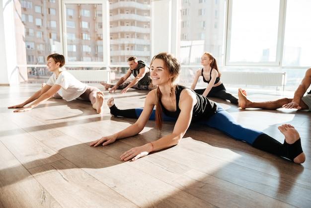 Grupo de pessoas, esticando e fazendo barbante no estúdio de yoga