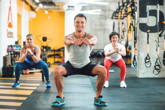 Grupo de pessoas fazendo exercício de aquecimento no clube de fitness