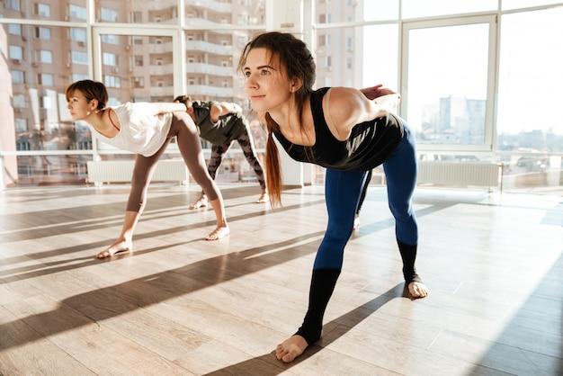 Grupo de pessoas fazendo exercícios com os pés descalços no estúdio de yoga
