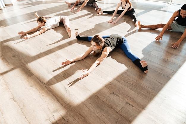 Grupo de pessoas fazendo exercícios de alongamento no estúdio de yoga