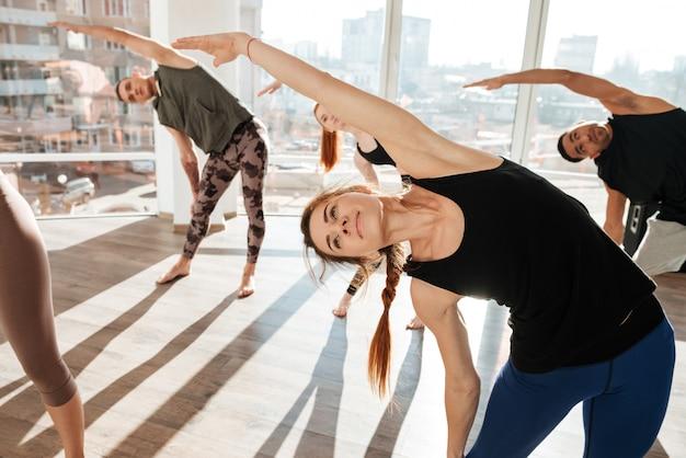 Grupo de pessoas fazendo exercícios na aula de yoga