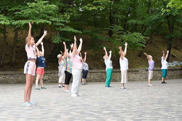 Grupo de pessoas fazendo ioga no parque. exercícios de respiração ao ar livre.