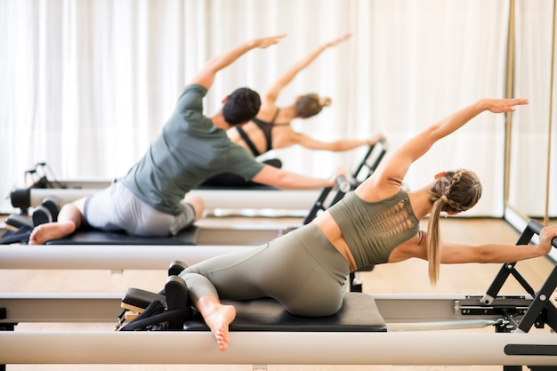Grupo de pessoas fazendo o exercício de sereia pilates