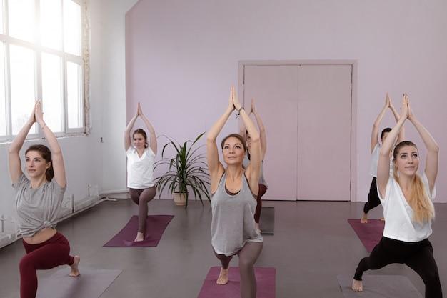 Grupo de pessoas fazendo pose de guerreiro ioga no ginásio