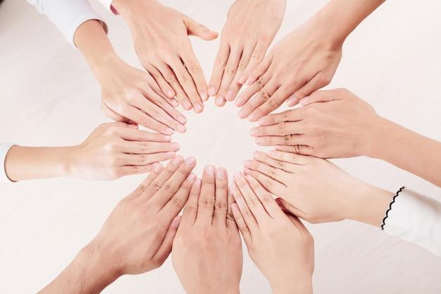 Grupo de pessoas fazendo sol com as mãos