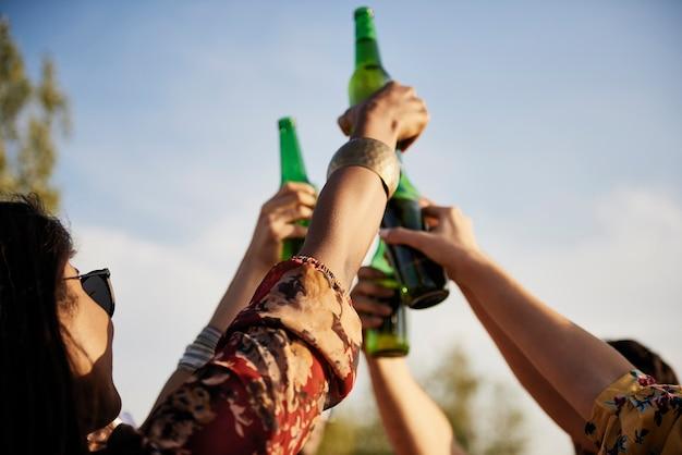 Grupo de pessoas fazendo um brinde de comemoração com garrafas de cerveja