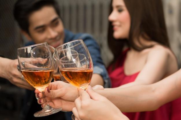 Grupo de pessoas fazendo um brinde juntamente com a desfrutar da festa à noite.