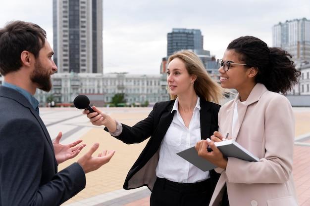 Grupo de pessoas fazendo uma entrevista para o noticiário