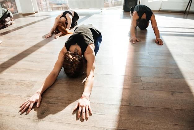 Grupo de pessoas fazendo yoga no chão de madeira em estúdio