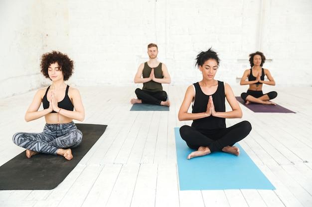 Grupo de pessoas fazendo yoga no ginásio, sentado em esteiras de treinamento