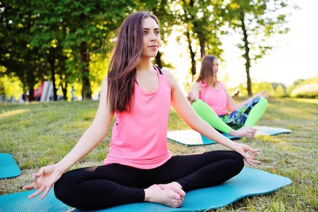 Grupo de pessoas fazendo yoga no verde com grama fresca ao ar livre. estilo de vida saudável