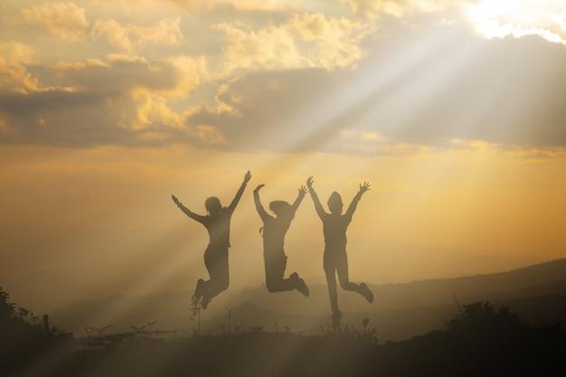 Grupo de pessoas felizes brincando no pôr do sol de verão na natureza