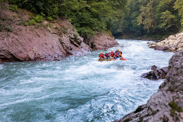 Grupo de pessoas felizes com guia whitewater rafting e remo no rio.