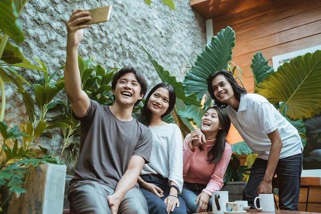 Grupo de pessoas felizes e sorridentes tirando um autorretrato em um café ao ar livre