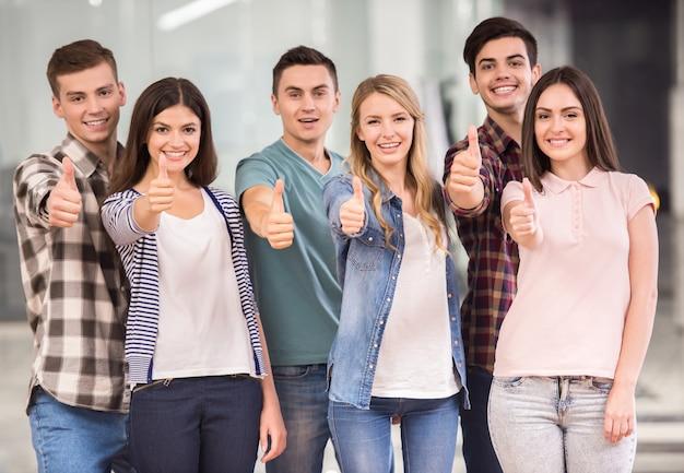 Grupo de pessoas felizes em pé e mostrando os polegares.