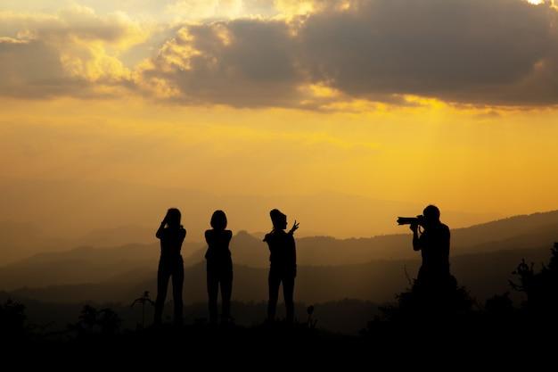 Grupo de pessoas felizes fotografando na montanha ao pôr do sol